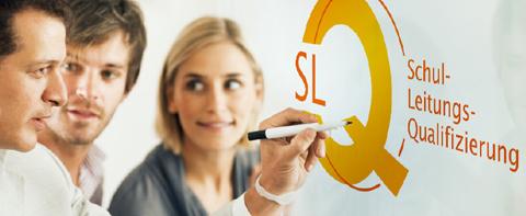 Drei Männer und eine Frau. Einer der Männer hält einen Stift in der Hand und schreibt auf ein Whiteboard das SLQ Logo